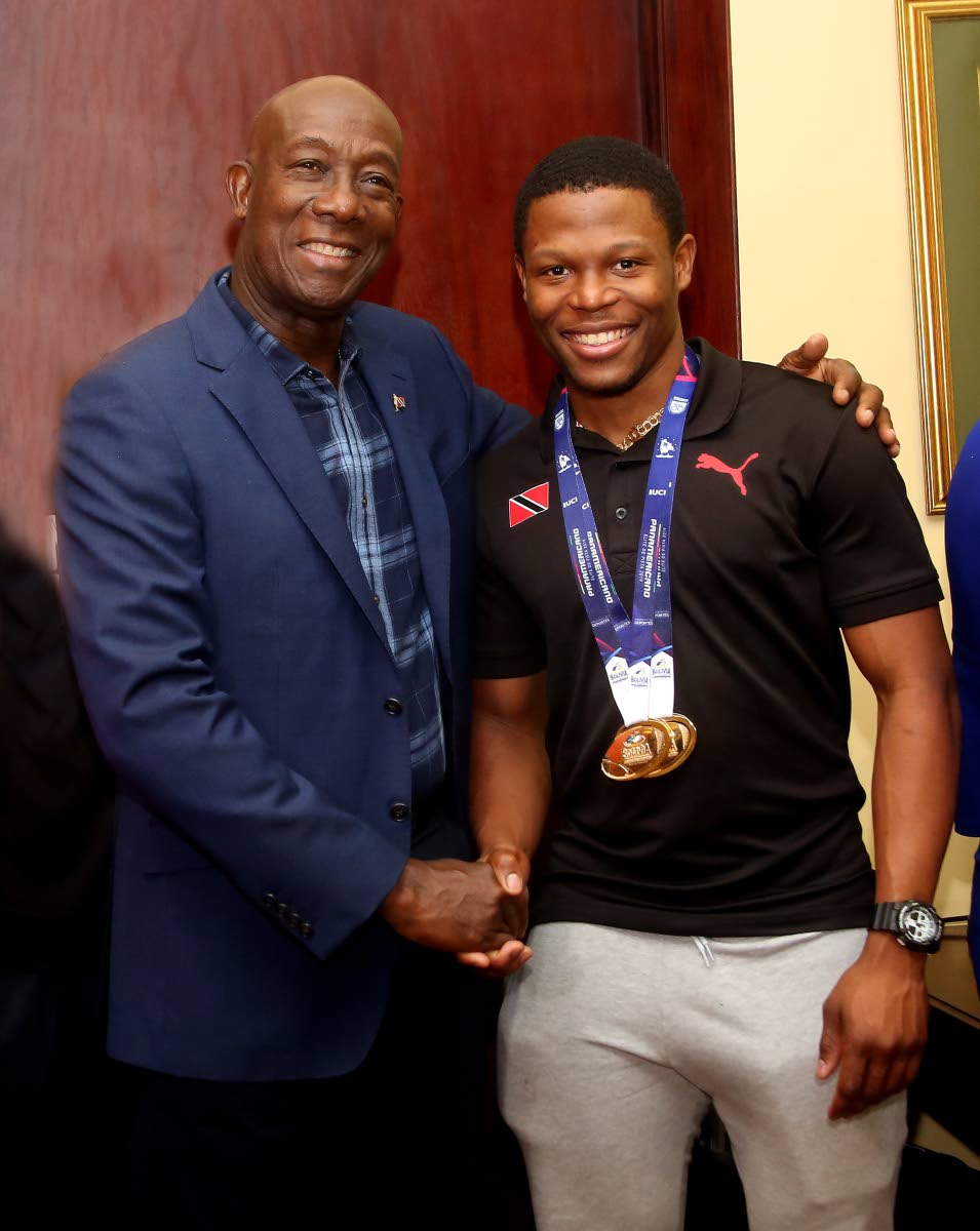 Prime Minister Dr Keith Rowley,left,greets world record holder and Pan Am gold medallist Nicholas Paul, at the VIP Lounge, Piarco Airport, on Tuesday night. Paul won gold, at the Pan American Track Cycling Championships, in Lima, Peru last Friday, with a new world standard of 9.1 seconds in the men's fly sprint 200m.