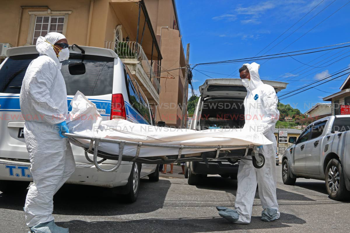 Undertakers remove the body of a bandit killed during an attempted robbery at the corner of Sutten and Cipero Streets in San Fernando on Wednesday. PHOTO BY MARVIN HAMILTON