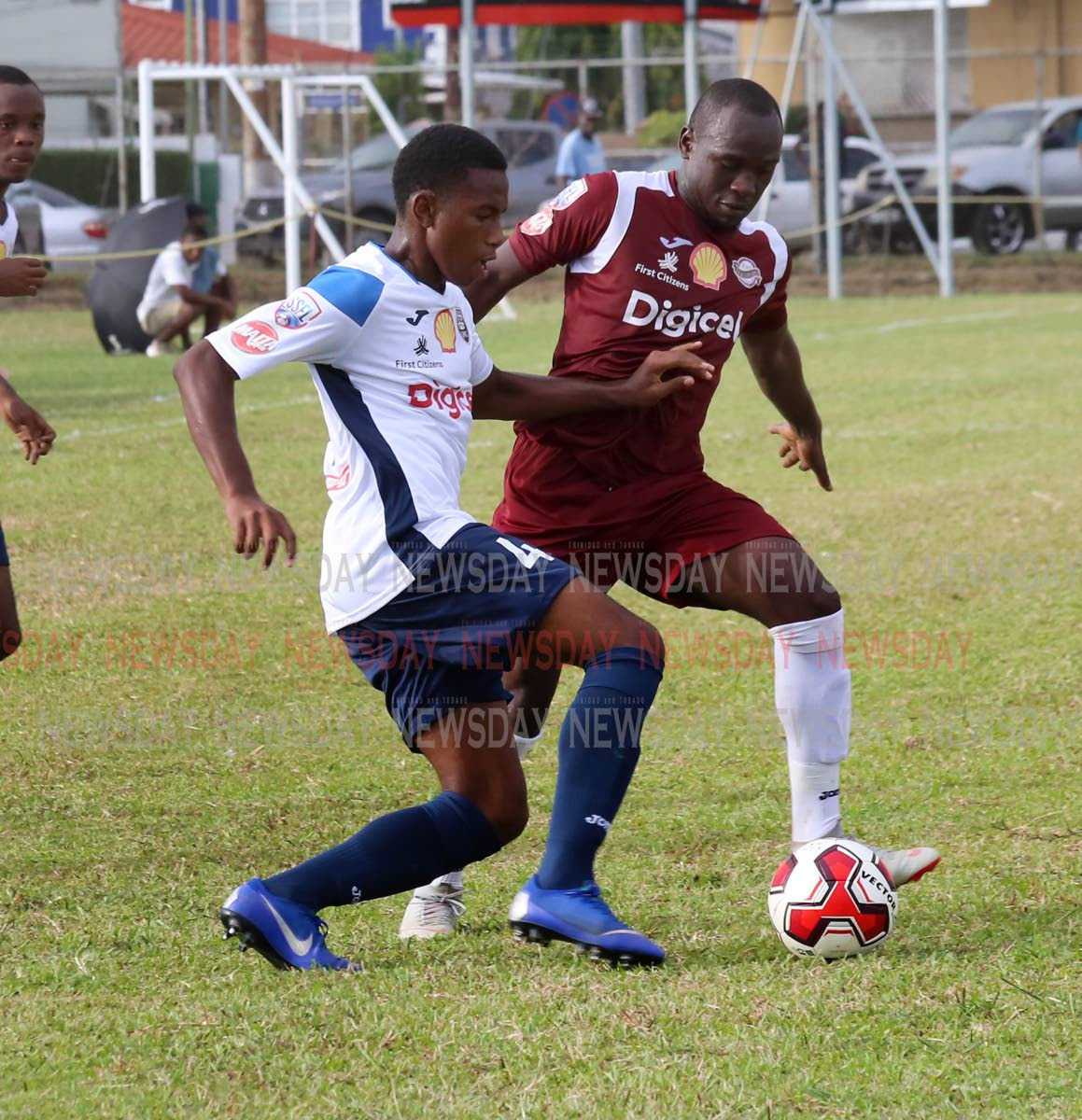 Mucurapo East's Jaheim Patrick,right, and Queen's Royal College's Ezekiel Armstrong battle for the ball in the SSFL opener,at Fatima Grounds, Mucurapo. PHOTO BY SUREASH CHOLAI