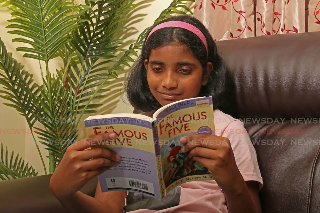 Siri Vadlumudi reads Famous Five, one of the books by her favourite author Enid Blyton, at home in Gulf View, La Romaine. PHOTOS BY MARVIN HAMILTON