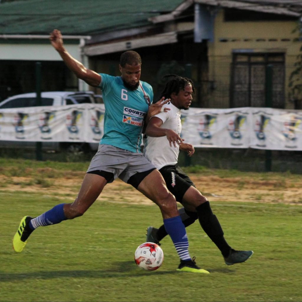 Morvant Caledonia AIA defender Radanfah Abu Bakr (left) screens off Kishon Hackshaw of Terminix La Horquetta Rangers, during a recent match in Division One of the Ascension Invitational Football Tournament, at the La Horquetta Recreation Ground, Arima.