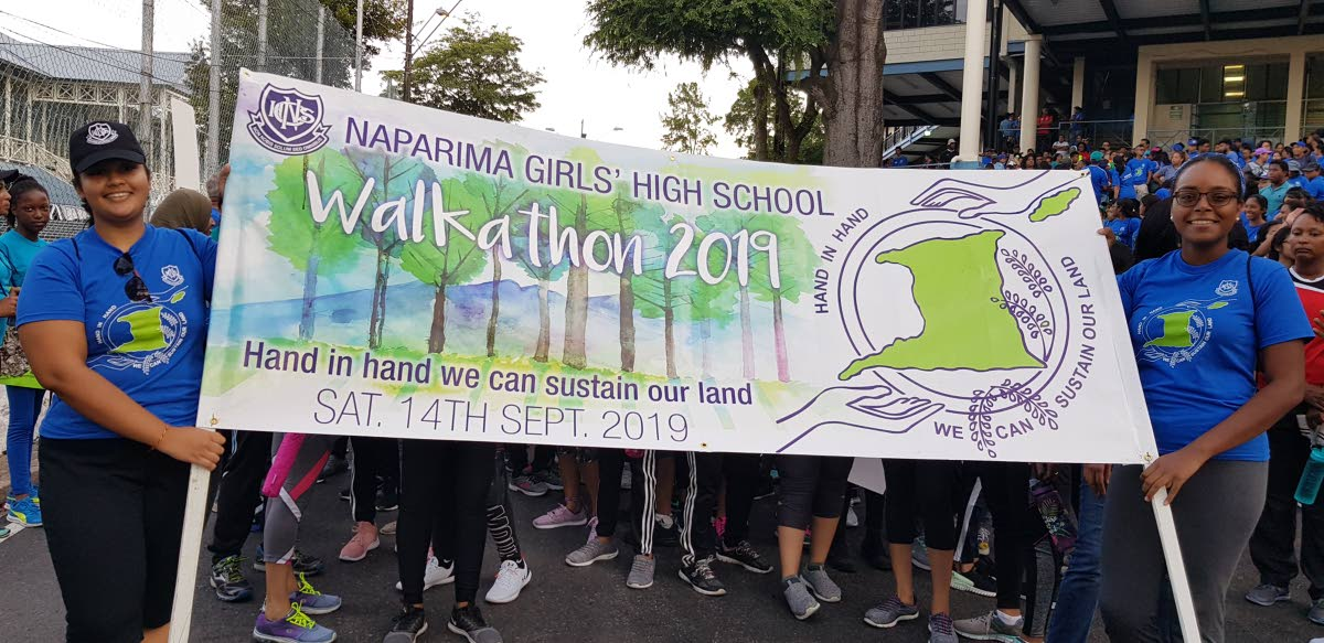 Naparima Girls' High School students raise awareness on protecting the environment during a walkathon in San Fernando on Saturday.