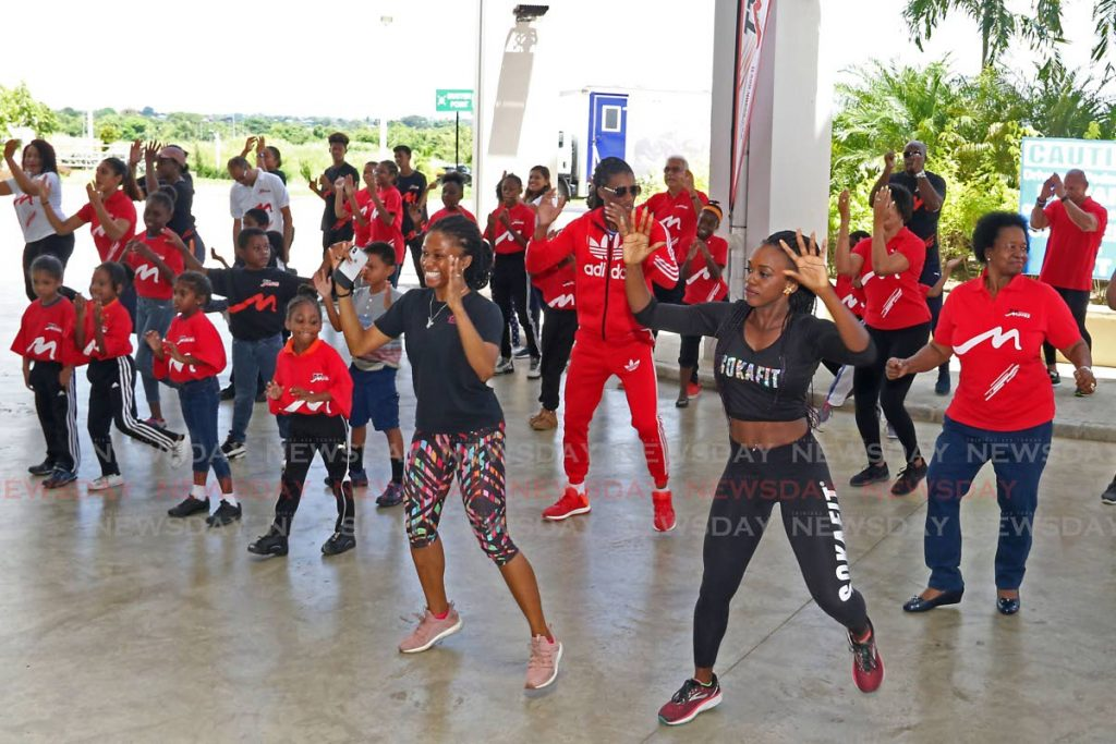 Fitness instructors exercise with children and their relatives at the launch of TT Moves 100% Wellness Challenge at Couva Hospital and Multi-Purpose Health Facility on Saturday.