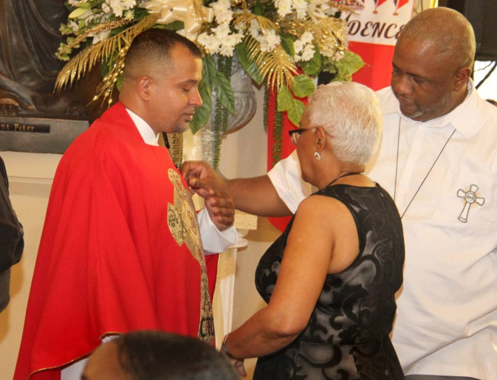 Visually impaired priest Mikkel Trestrail is vested by Brother Kyle Dardaine while his mother Valerie looks on during his ordination at the Cathedral of the Immaculate Conception, Port of Spain.