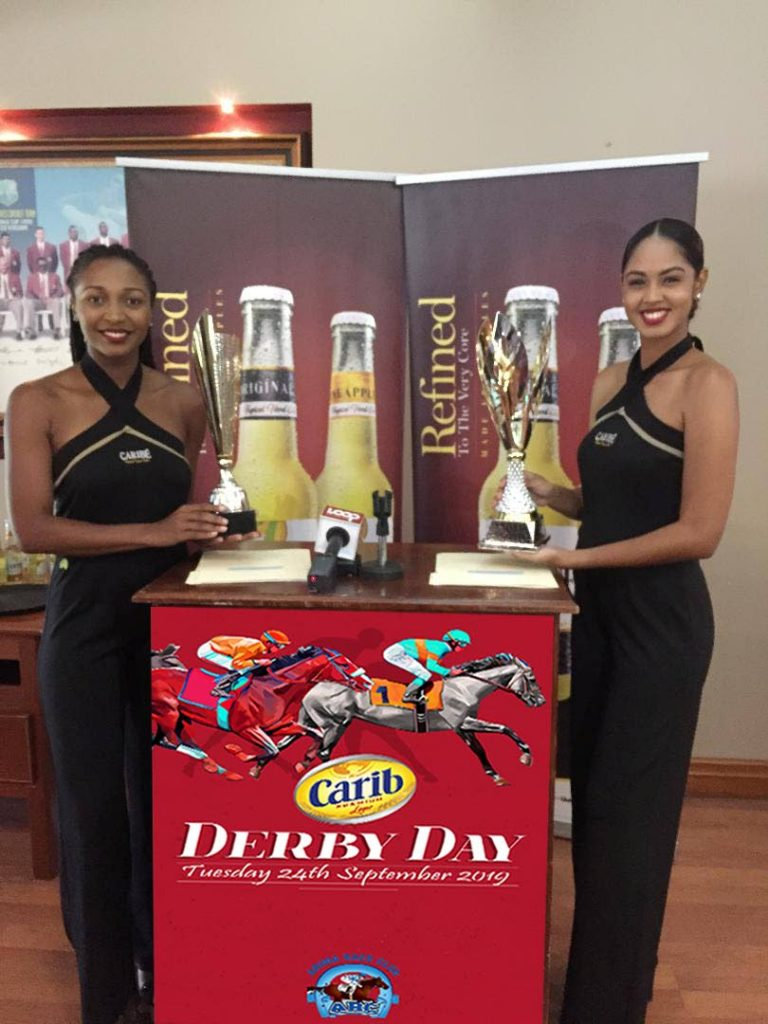 A pair of Carib Ladies with the respective Carib Brewery Derby and Carib Brand Diamond Stakes trophies, at yesterday's draw for post positions, at the Ansa McAl Hospitality Suite, Queen's Park Oval. PHOTO COURTESY ARC FACEBOOK PAGE.