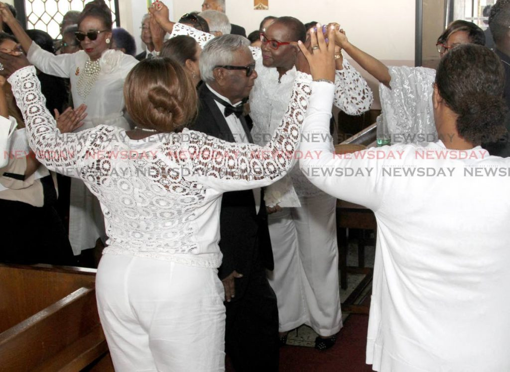 Planning Minister Camille Robinson-Regis, centre in white, forms part of an honour guard with Joan Yuille-Williams, left, and others at the funeral of Dr Linda Baboolal at All Saint's Anglican Church, Port of Spain on Monday as Baboolal's family members exit the church. PHOTO BY ROGER JACOB