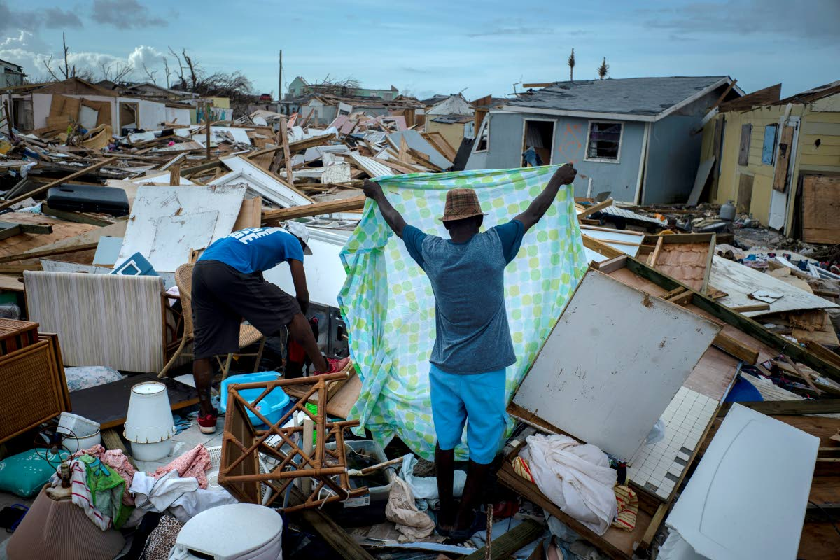Immigrants from Haiti recover their belongings from the rubble in their destroyed homes, in the aftermath of Hurricane Dorian in Abaco, Bahamas. AP PHOTO