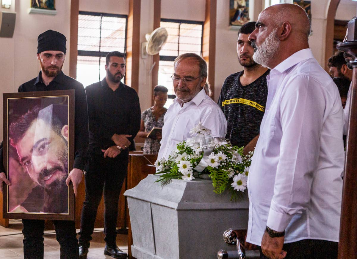 FINAL RITES: Relatives of Elias Dabbourah at his funeral yesterday at the St Joseph's RC Church in Bacolet, Tobago.