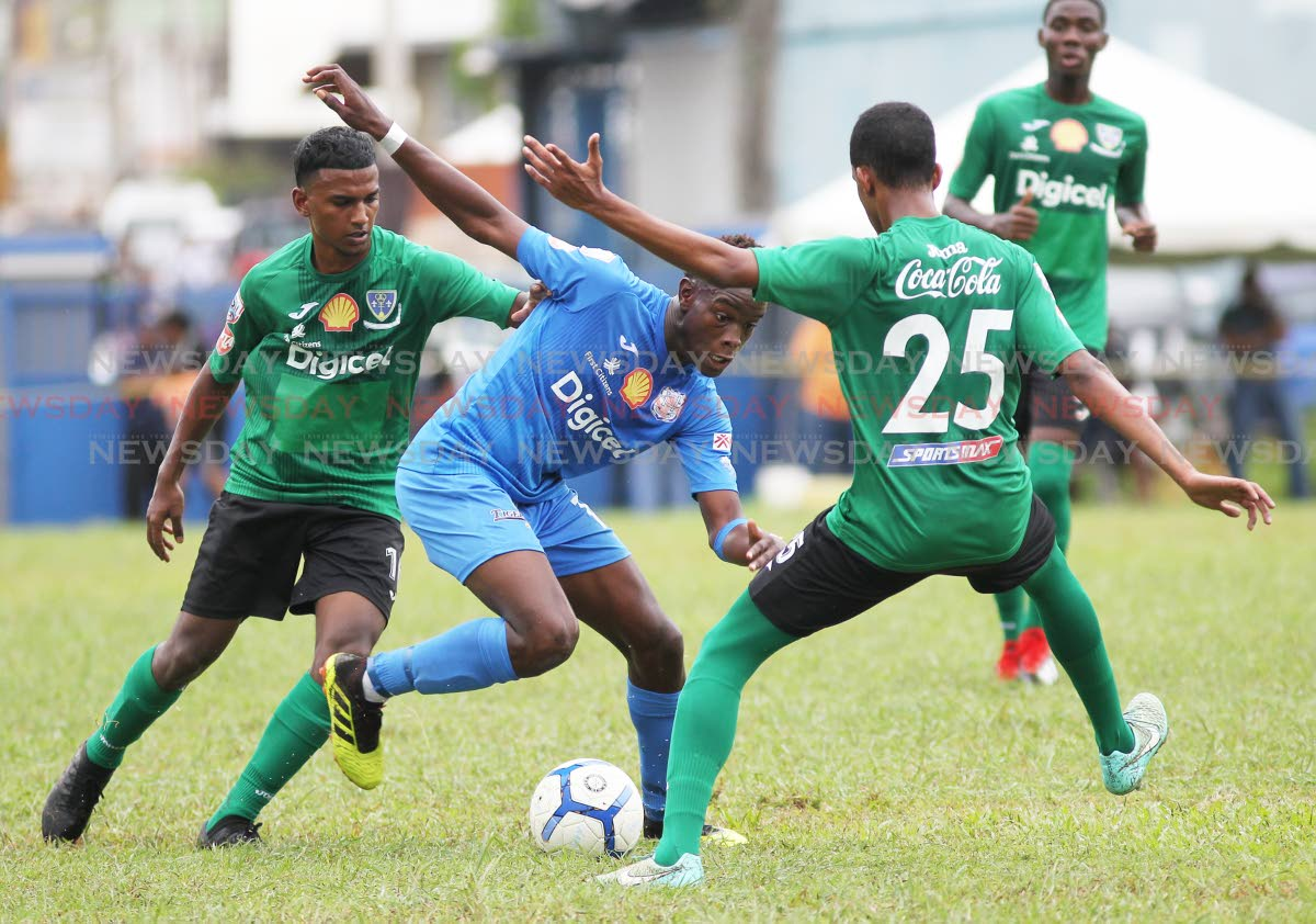Naparima College player Decklan Marcelle (C) tries to evade Symron Wiseman(R) of St Bendict's College,during the Secondary Schools Football League match,held at Lewis Street,San Fernando,yesterday.