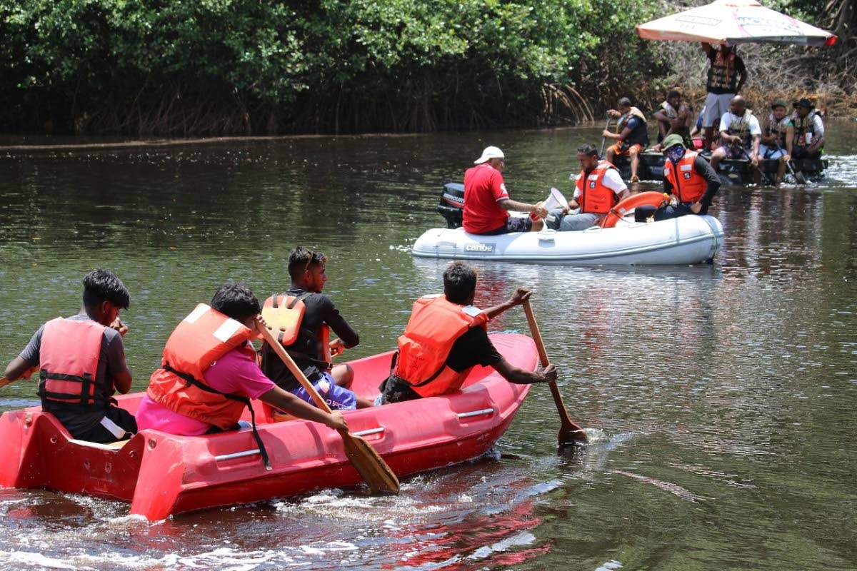Raft derby teams paddle down the  Mitan River, Manzanilla.