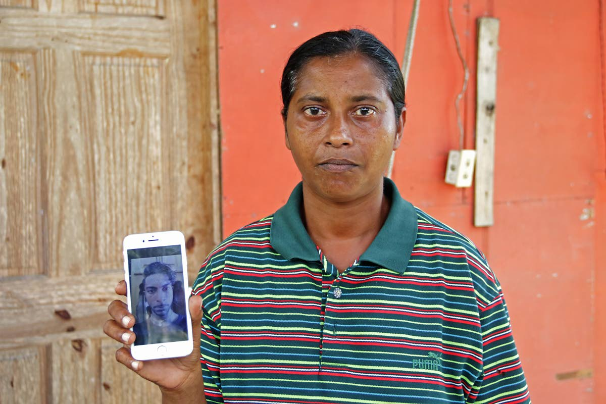MY BROTHER'S DEAD: Reena Ramcharan displays a photo of her brother Besham on her cellphone hours after he was found stabbed to death at his home in Princes Town yesterday. PHOTO BY MARVIN HAMILTON