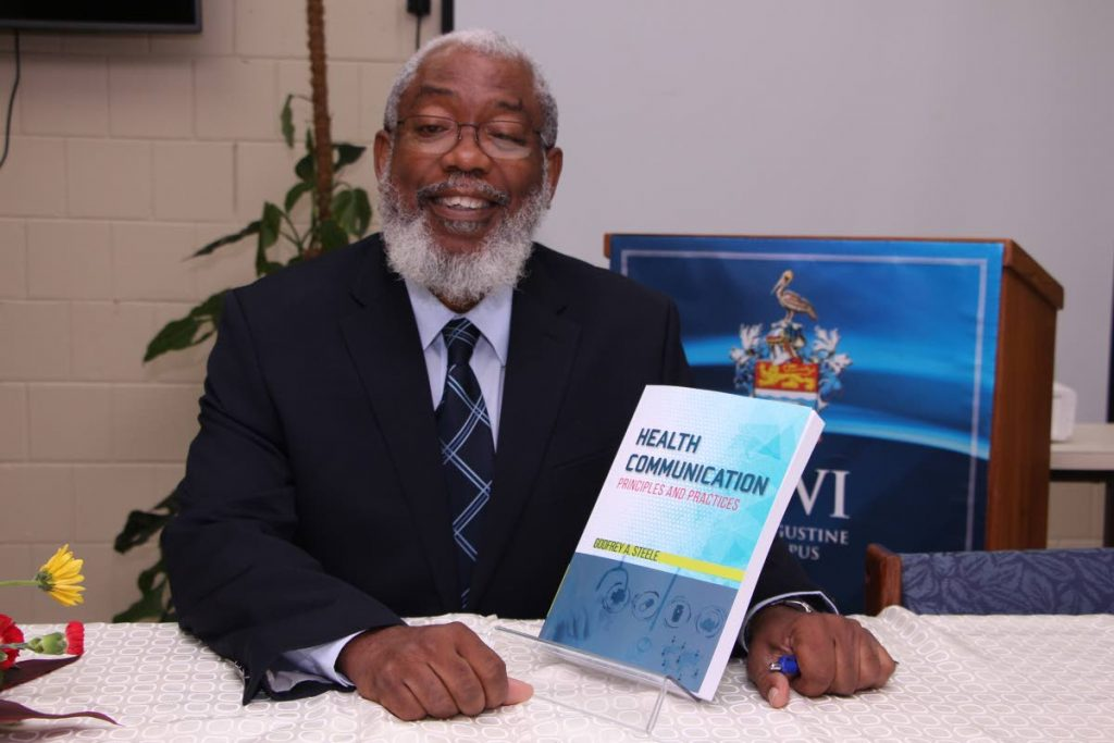 Dr Godfrey Steele with a copy of his book Health Communications: Principles and Practice. PHOTO COURTESY UWI
