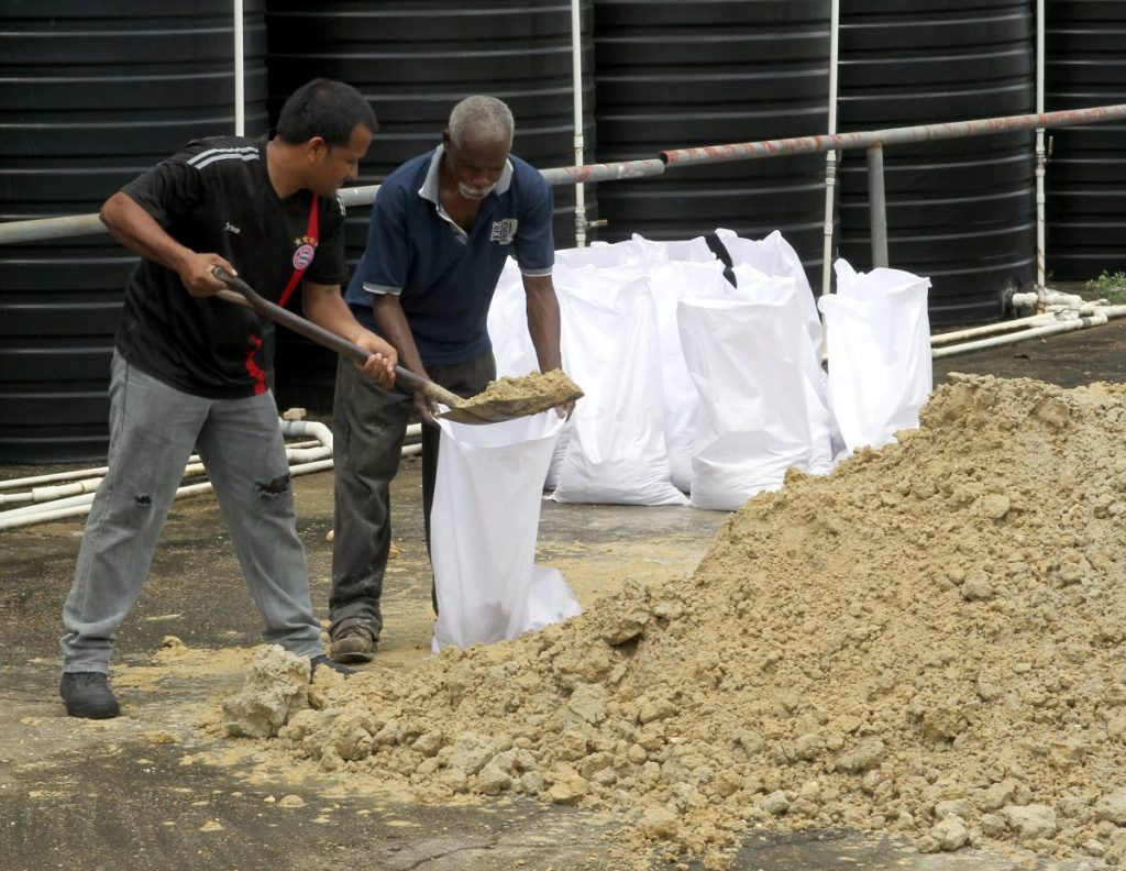 Ensacado de arena: los trabajadores de la fábrica Ven Caribbean Paper preparan sacos de arena para usar como barreras en las entradas de la fábrica en La Horquetta después de que TT fue puesto en alerta de clima severo ayer. FOTO POR ROGER JACOB.