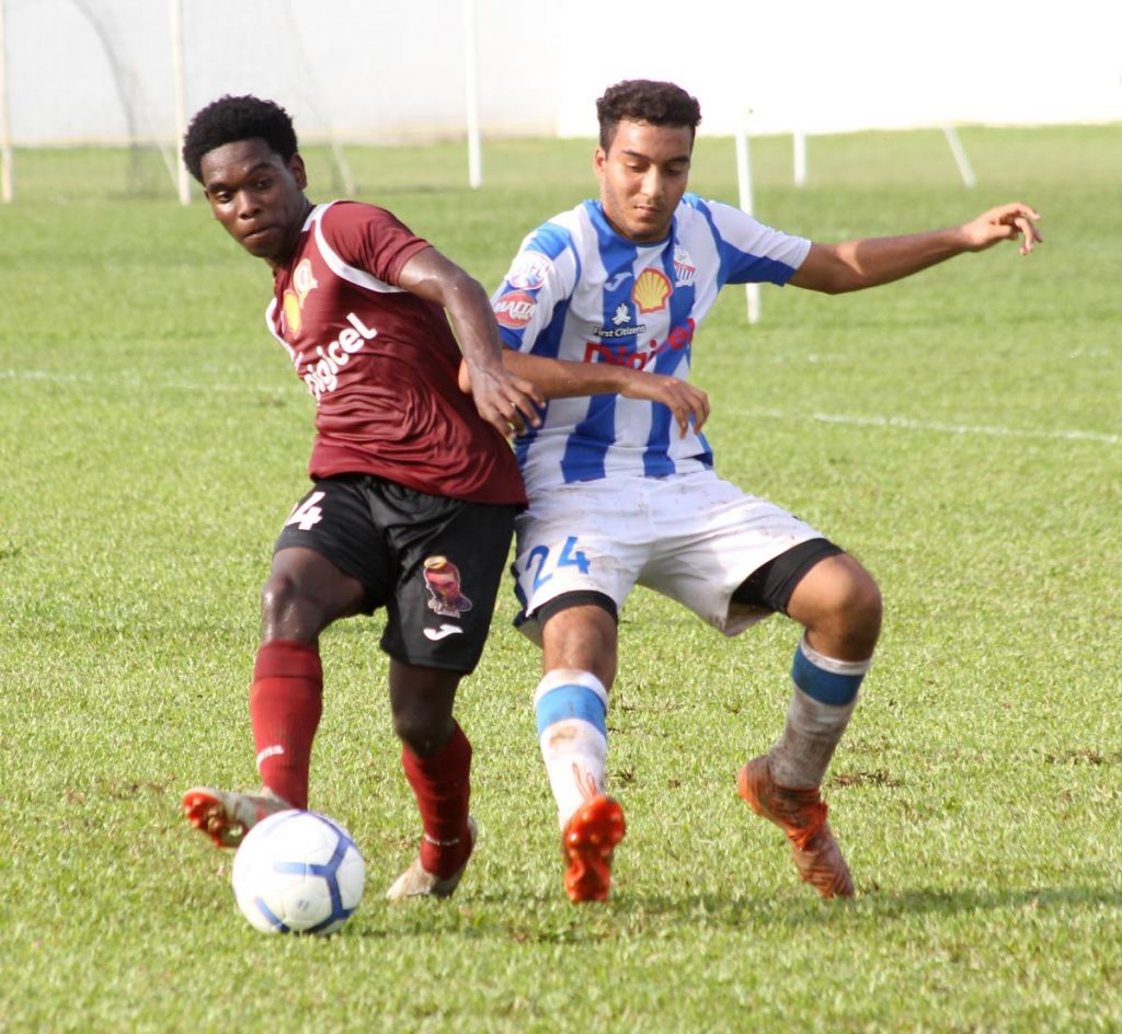 Adonis Andrews of St Mary's College, right, and Pleasantville Secondary's Dillion Yearwood battle for possession in a SSFL Premier Division match at St Mary's College Ground in St Clair, yesterday. PHOTO BY ROGER JACOB