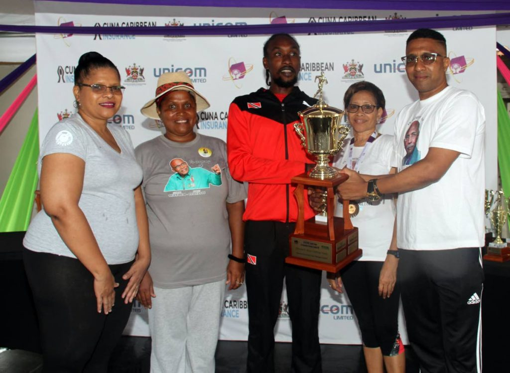 Local runner Sherwyn Stapelton of Trinidad and Tobago Runners Club, centre, collects the Desmond Baxter challenge trophy from Dale Baxter, son of Desmond Baxter, yesterday. Stapleton emerged the overall and local winner of the Venture Credit Union 5K, which started in front of Venture Credit Union office in Couva. Alos pictured are (from left) Baxter's daughters Diane, Doreen and Dorinda.