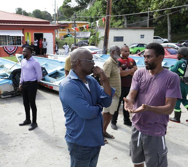 THA Chief Secretary Kelvin Charles, left, listens attentively to Tobago Powerboats and Aquatic Sports Association member, Lincoln Stewart, as he explains the plight of the 11 fishermen who lost their pirogues during the passage of TS Karen. PHOTO COURTESY THA