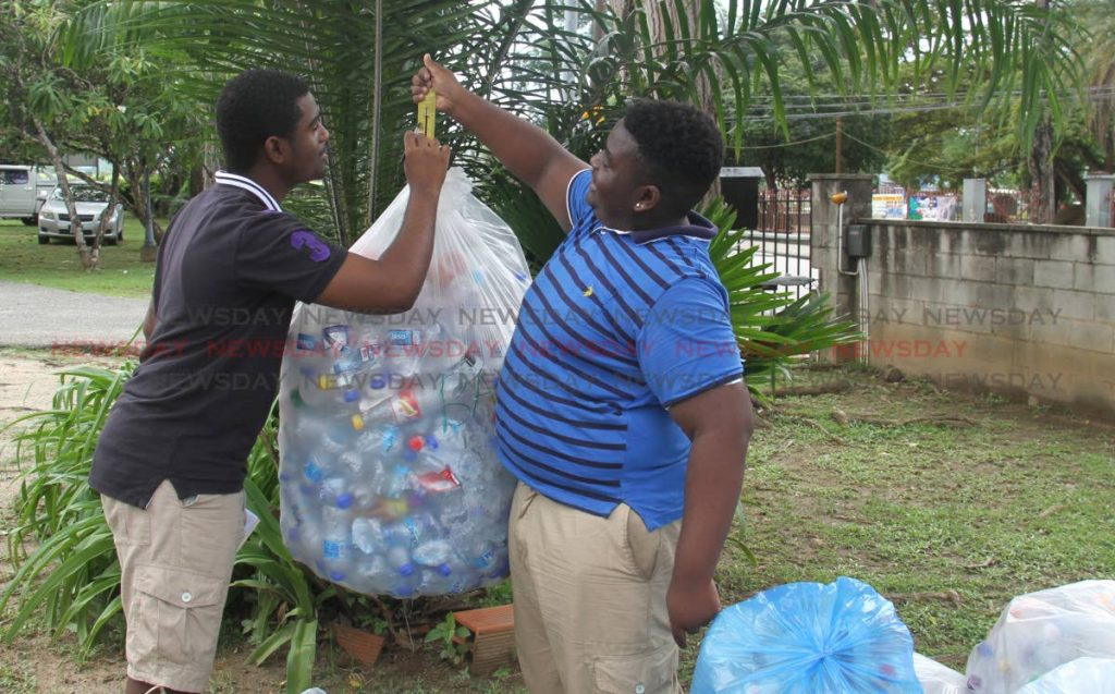 Brothers Isaiah and Xavier Villafana weigh recycled bottles at Hayes Court yesterday.  PHOTO BY AYANNA KINSALE