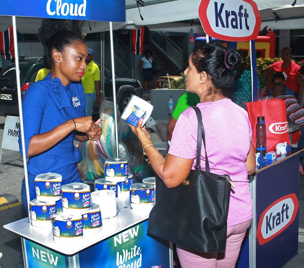 In this August 2019 file photo, customer service representative interacts with a customer at JTA supermarket in San Fernando.