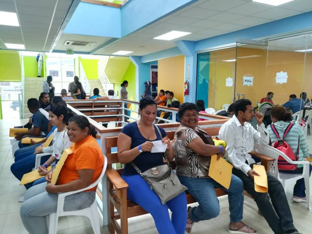 In this June 15. 2019 file photo Venezuelans wait at Port Mall, Milford Road, Scarborough, Tobago to register for a one-year amnesty to work in TT.