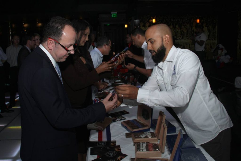 CIGAR TALK: Cesar Alvarez, right, shows British High Commissioner to TT Tim Stew different types of cigars at the launch of the Cigar Festival at the Old Havana Cigar Lounge, Queen's Park East on Wednesday.