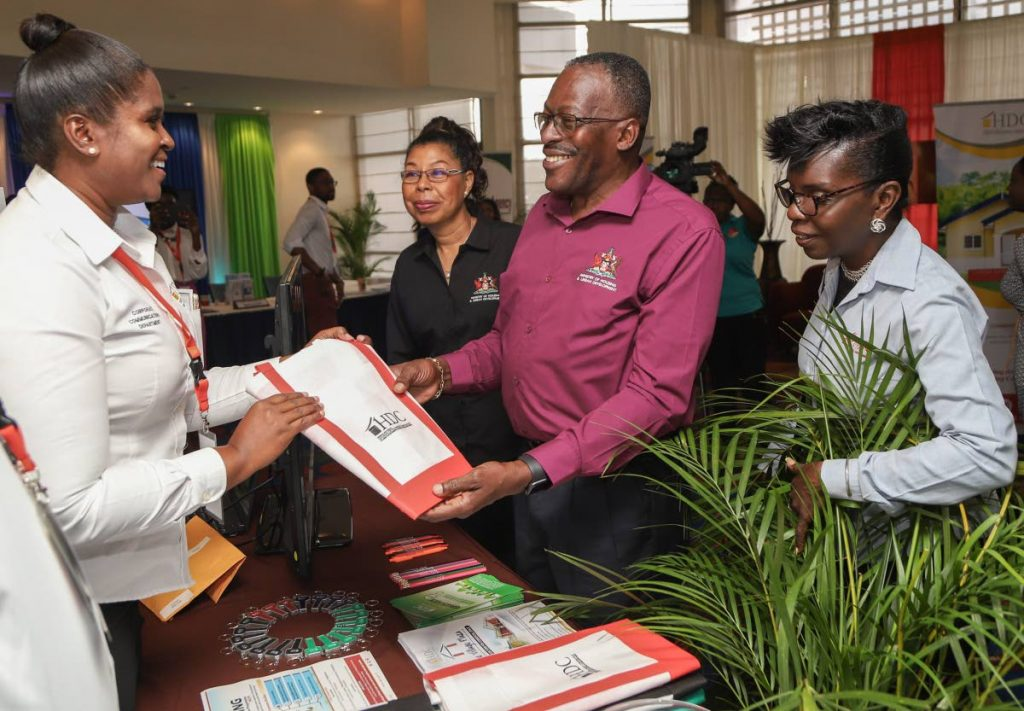 Housing Minister Edmund Dillon interacts with HDC staff at the Housing 101 Expo held by the Ministry of Housing at Hilton Trinidad, St Ann's yesterday. PHOTO BY JEFF K MAYERS