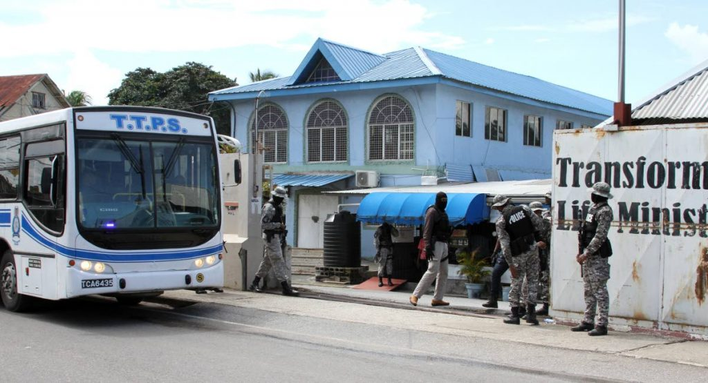 Members of the TTPS secure the compound of the Transformed Life Ministries Centre, where they conducted a raid.  PHOTO: ANGELO M. MARCELLE
