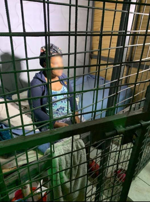 BEHIND BARS: A woman is seen in this photo, uploaded to social media, sitting in a caged enclosure at an Arouca church which was raided by police yesterday who removed 69 people found locked in cages on the ground floor of the compound.
