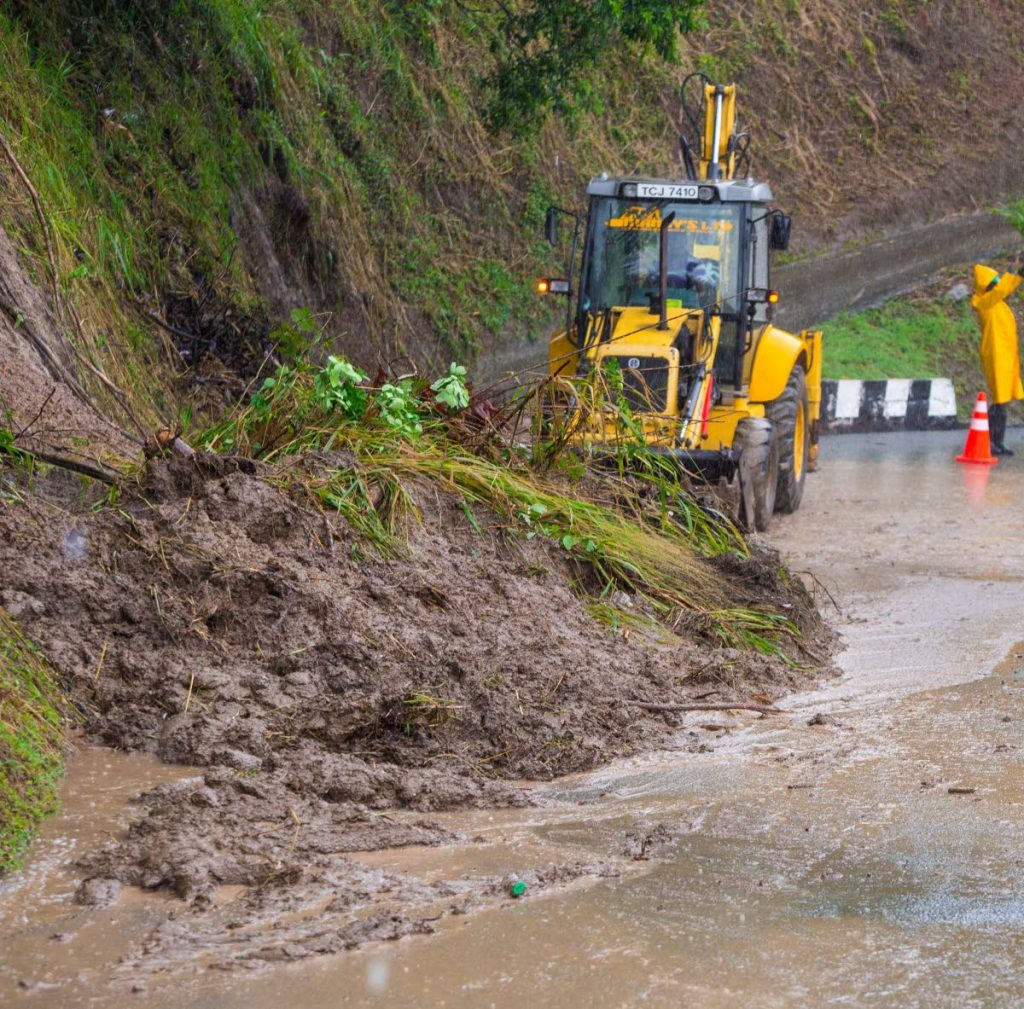 A backhoe helps clear the roadway after a landslide in Moriah on Wednesday.
