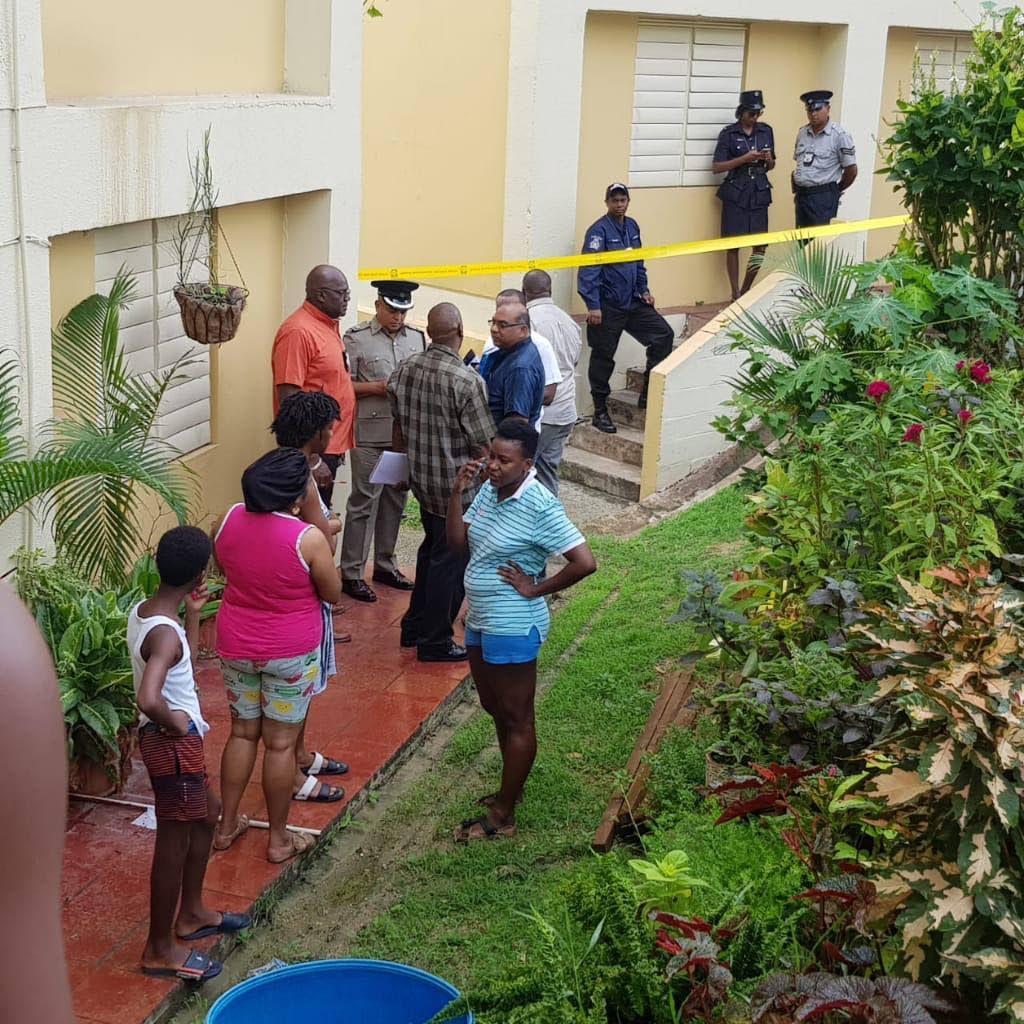 Snr Supt Wayne Mohammed with residents of Building C, Embacadere, San Fernando, where Ezekiel Daniel was murdered last night