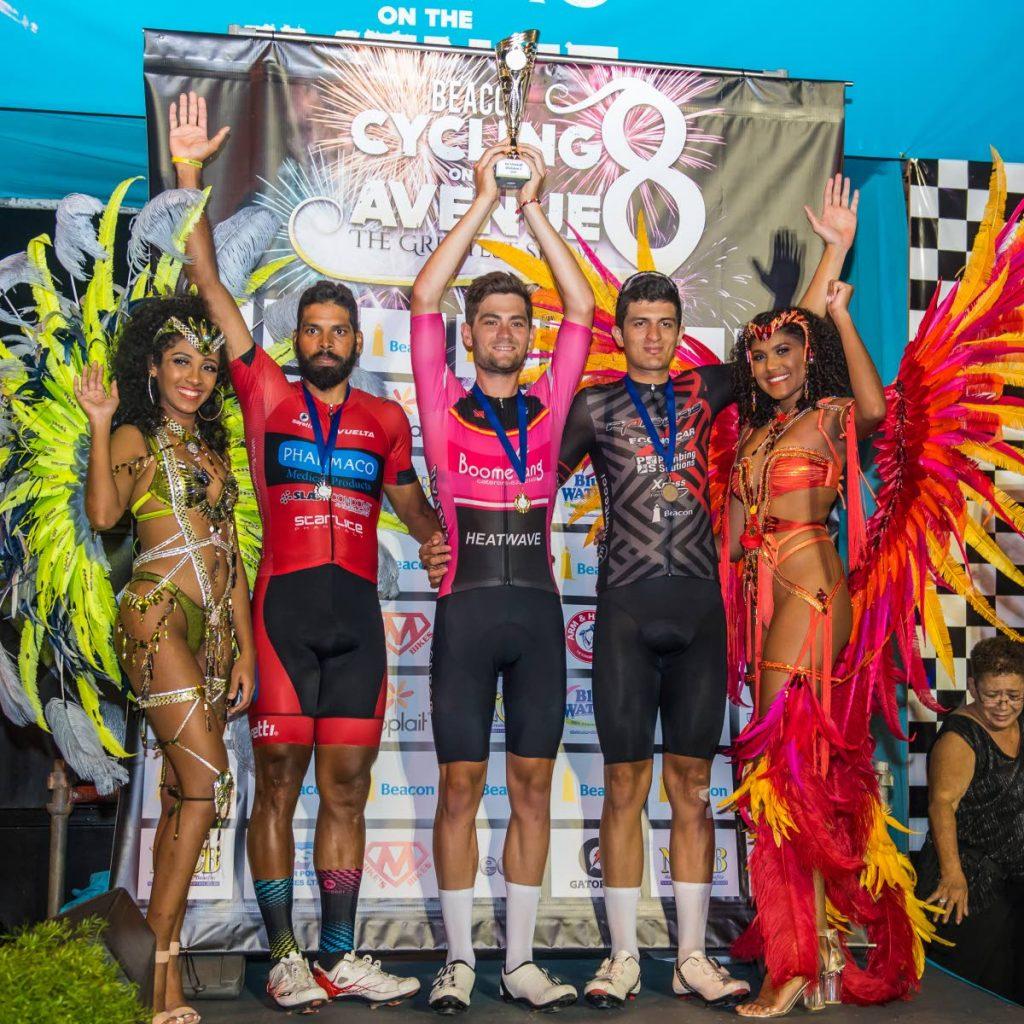 Joel Yates (centro), del Heatwave Cycling Club, levanta el trofeo del ganador en la carrera Beacon Cycling on the Avenue del miércoles. Frank Travieso (segundo desde la izquierda) colocó en segundo lugar y Brian Gómez (segundo desde la derecha) de Raiders quedó en tercer lugar. Foto por Elliot Francois