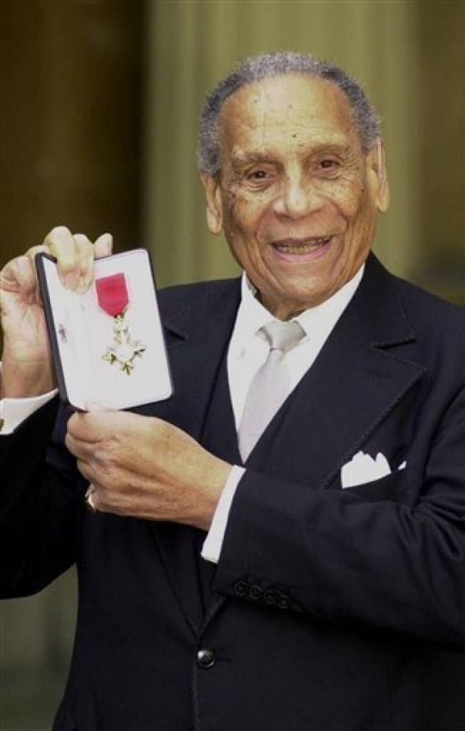 A March 21, 2000, file photo of band leader Edmundo Ros after receiving an OBE for services to entertainment during an investiture ceremony held at Buckingham Palace, London. (AP Photo/John Stillwell/PA)