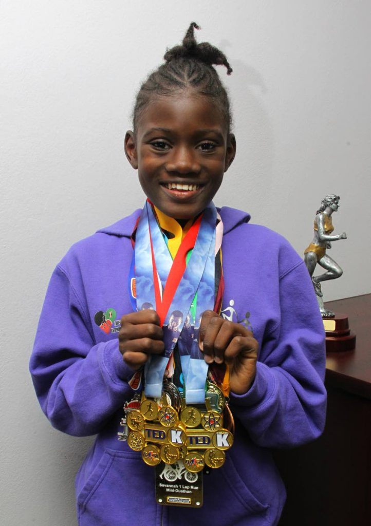 Aniqah Bailey proudly shows some of the medals she has won in 5K races, defeating adult runners, during a visit to Newsday, Port of Spain, recently. PHOTO BY ROGER JACOB  - ROGER JACOB