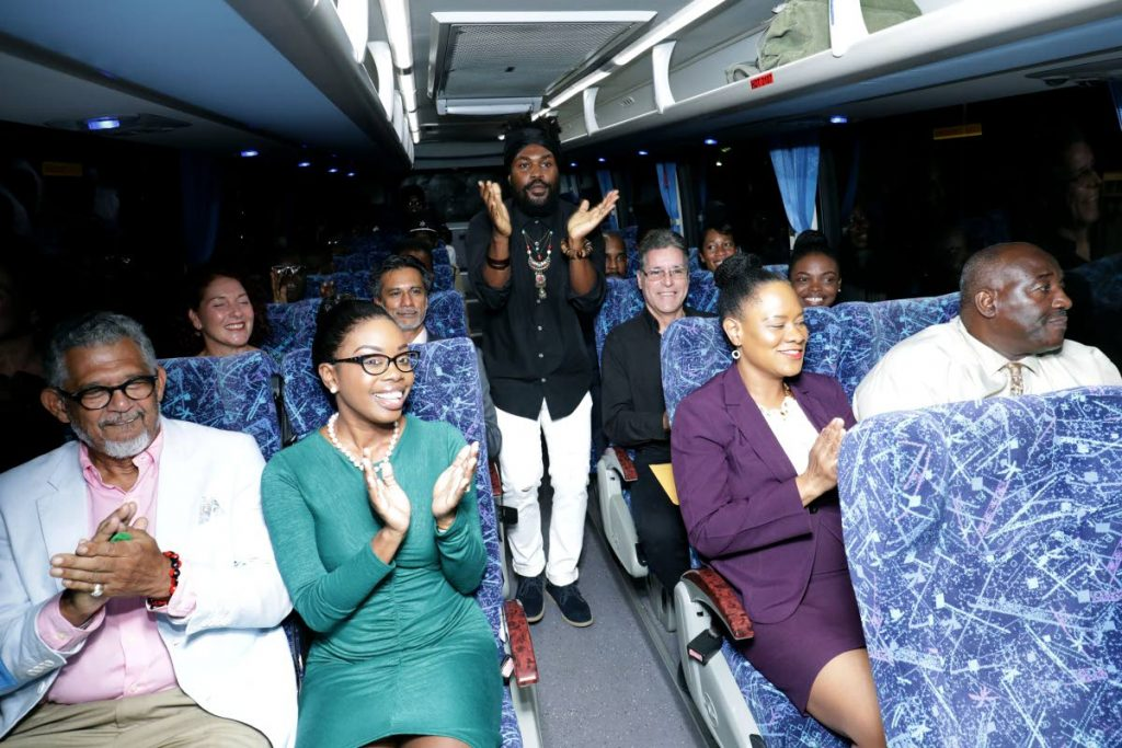 Artiste Khalem 'JaMoi' Alexander sings the Know Your Country Bus Tour jingle as he entertains guests on board one of the buses to be used by the PTSC for the tours. Seated, from left, in foreground are PTSC chairman Edwin Gooding, Tourism Secretary Nadine Stewart-Phillips, Tobago East MP and Minister of State in the Office of the Prime Minister Ayanna Webster-Roy and Adviser to the Settlements Secretary Theophilus Trim. - THA Info Dept