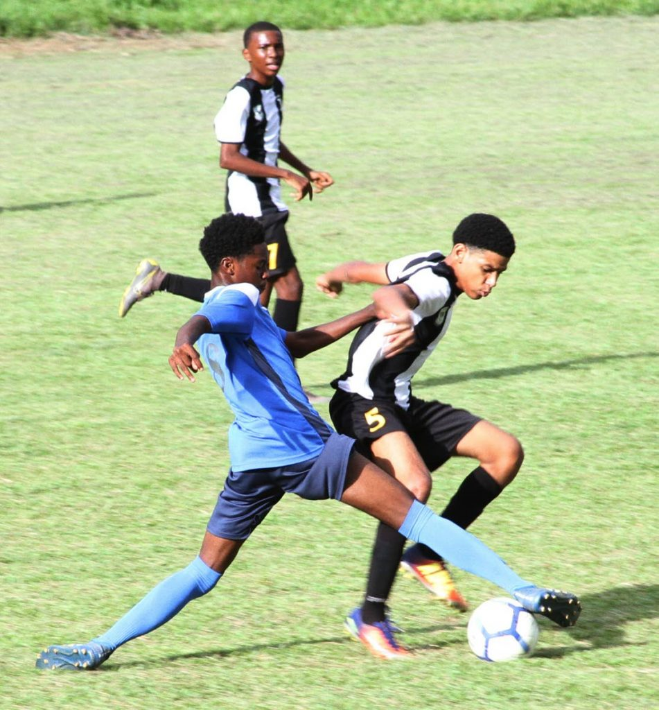 Mikel St. Martin of Holy Cross College(R) wards of a strong tackle for the ball from Dorian Jeffery of Arima North Secondary School,yesterday,during action in the Secopndary schools Football League East Zone match at Arima North's grounds.