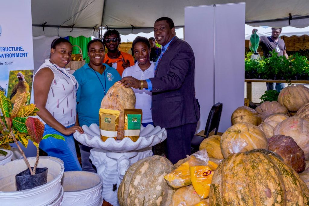 Sheldon Cunningham, right, Assistant Secretary, Division of Infrastructure, Quarries and Environment, with representatives of URP office, as they display agriculture produce for sale at World Food Day in Bacolet on Wednesday. PHOTO BY DAVID REID  - DAVID REID