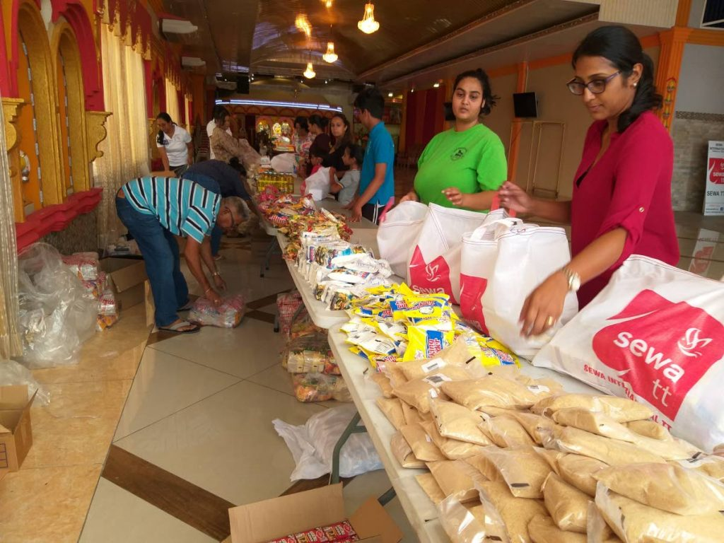 Volunteers of Sewa TT help prepare food packages to distribute to communities affected by flooding in the aftermath of tropical storm Karen. - Tyrell Gittens