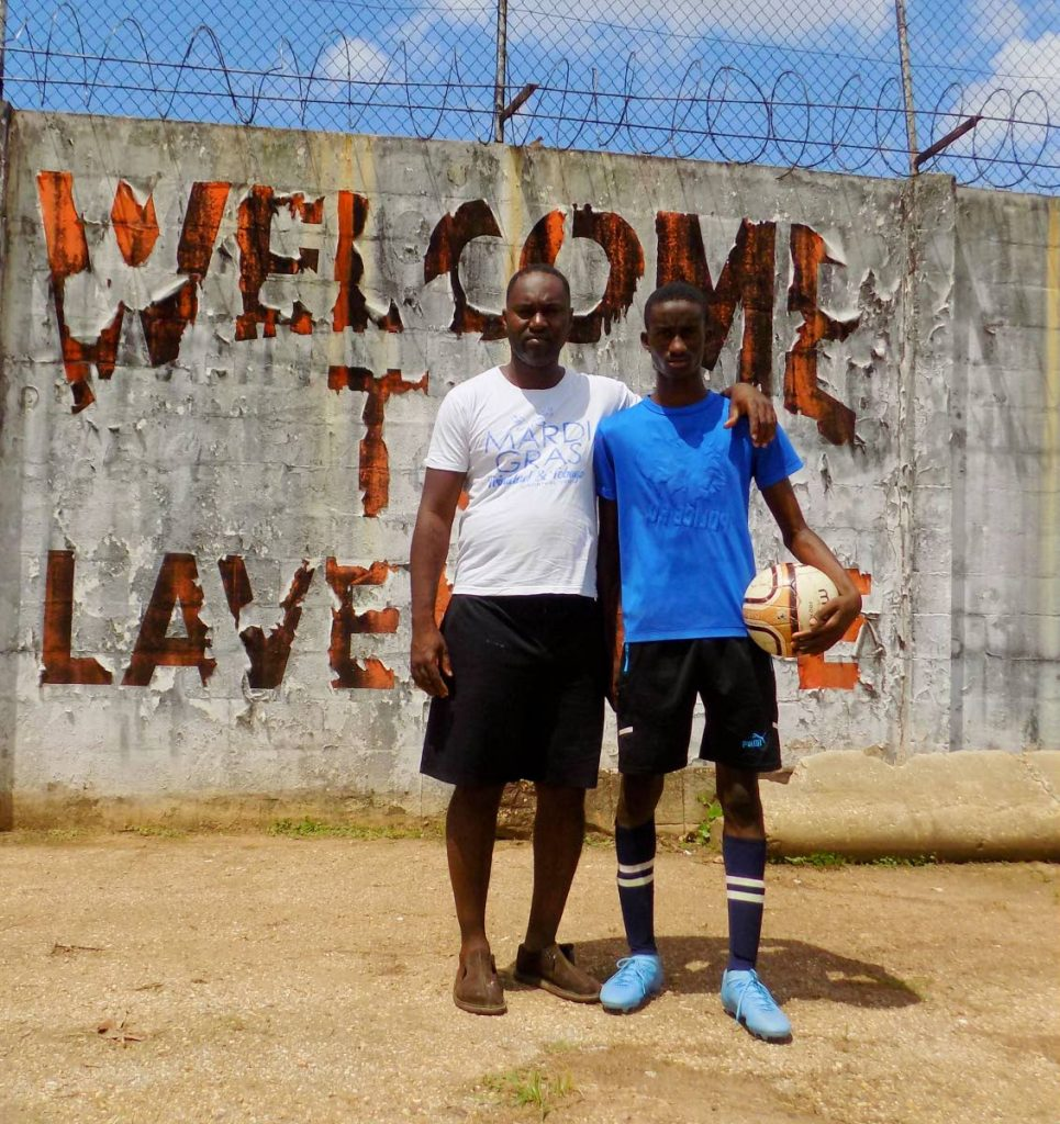 Fabien Ayres, right and his father Devon Ayres, pose in front of a sign at the Fernandes recreation field, Eastern Main Road, Laventille. - Shane Superville