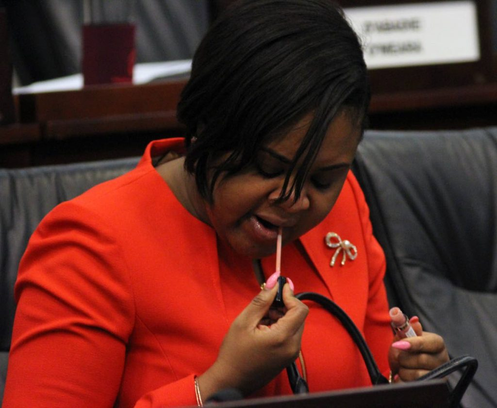 MAKE UP MINISTER: Tobago West MP and Sport Minister Shamfa Cudjoe applies some make up yesterday during the Parliament's Standing Finance Committee meeting.  - ANGELO_MARCELLE