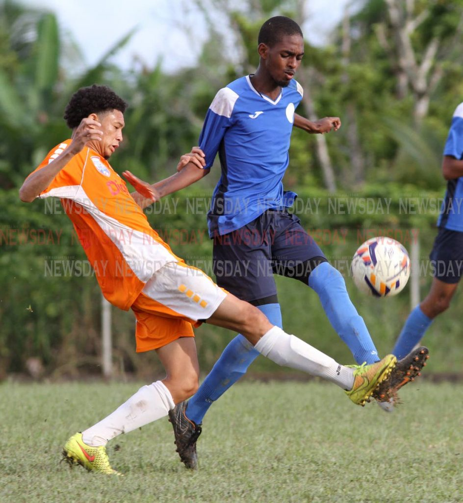 Valencia High School's Mikhail Mollino, (L) and Keyel James of Arima North Secondary, battle for the ball during the SSFL East Zone final ,at Valencia High on Tuesday afternoon. Arima won 3-2. - ANGELO_MARCELLE