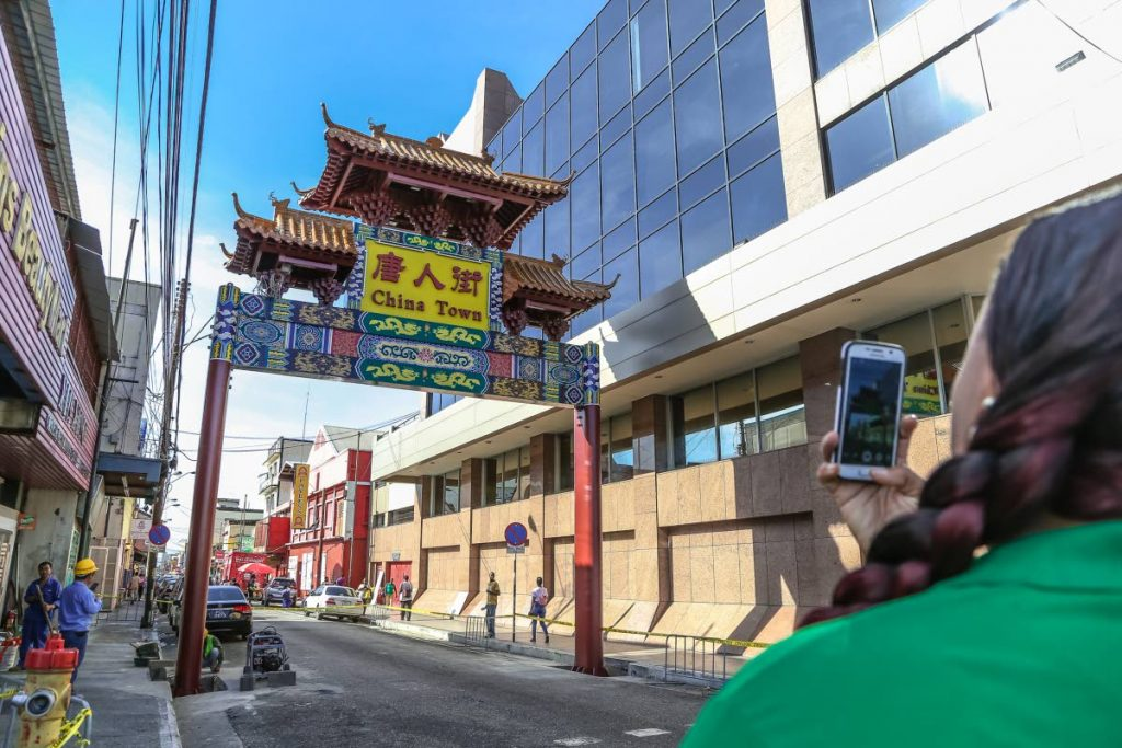 A passer by takes a picture of the newly erected Chinatown sign on Charlotte Street, near Park Street in Port of Spain. - JEFF K MAYERS
