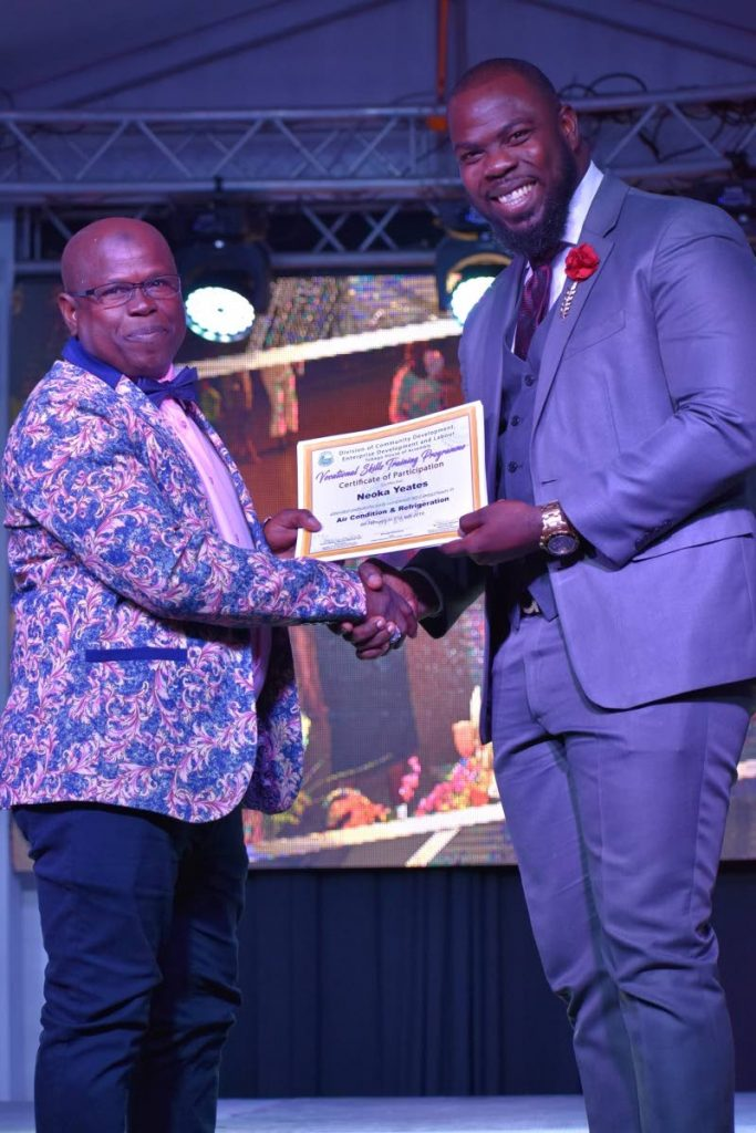 Shomari Hector, right, Assistant Secretary, Division of Community Development, Enterprise Development and Labour, hands out a certificate for completing the air conditioning and refrigeration programme.  - THA
