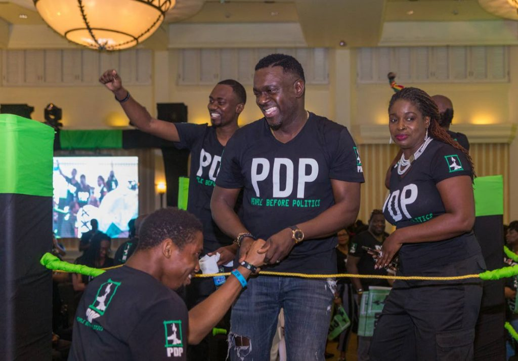 Watson Duke, centre, Farley Augustine left and Dr Faith BYisrael rejoice together on stage at PDP's election campaign launch last Sunday at Magdalena Grand Beach and Golf Resort, Lowlands. - DAVID REID