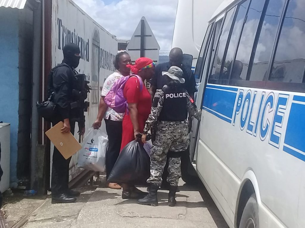 Police guide people into a van during what they described as a rescue operation at the Transformed Life Ministry in Arouca. Photo by Shane Superville