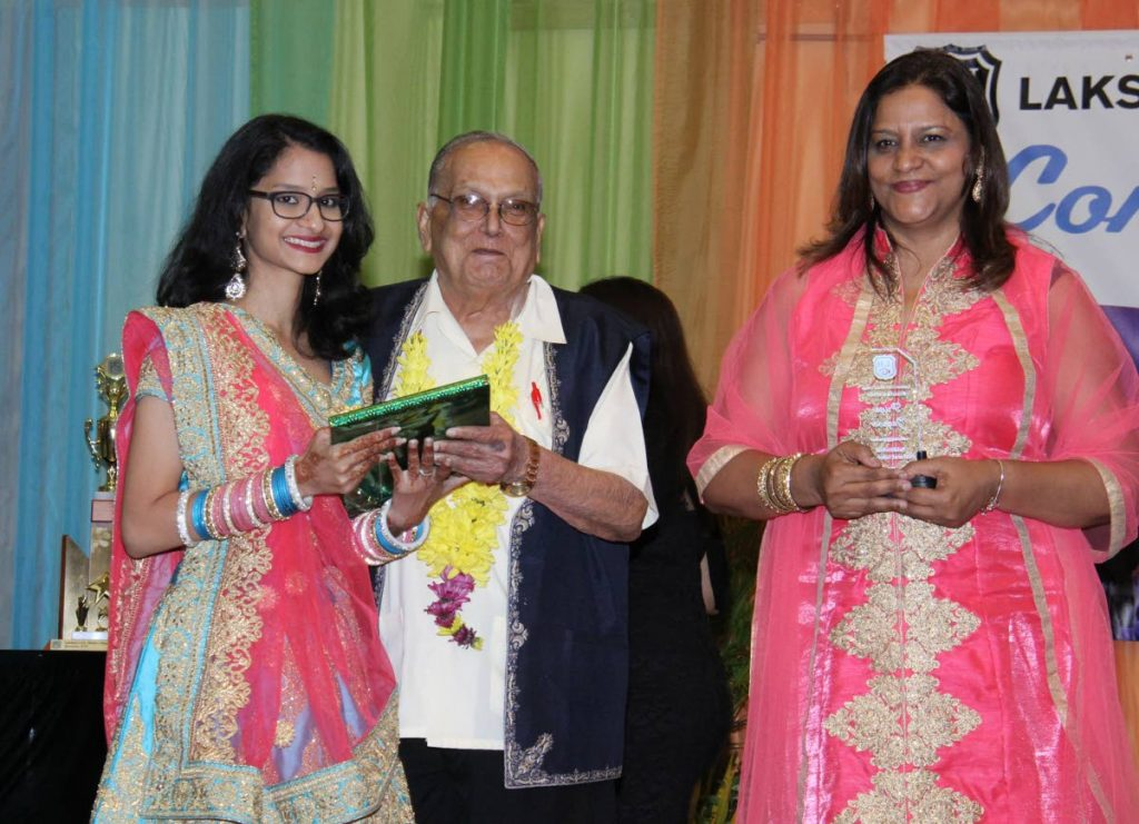 In this October 2018 file photo, scholarship winner Priya Jagroo receives a  prize and trophy Maha Sabha secretary general Sat Maharaj and Sonia Mahase-Persad, principal of Lakshmi Girls' Hindu College, St Augustine where Jagroo was a student. - ROGER JACOB