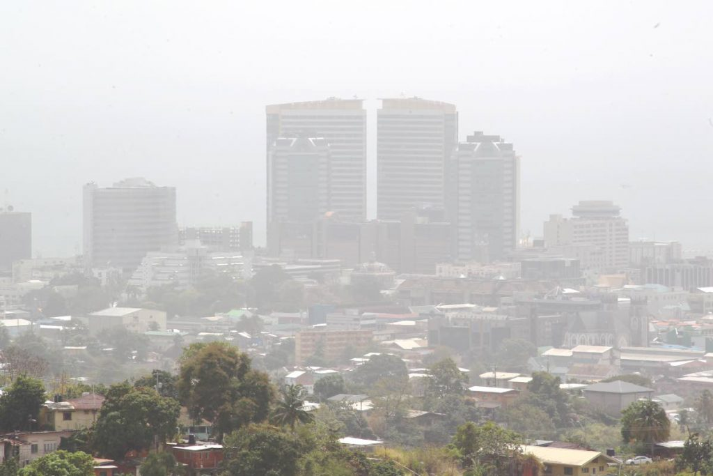 A view of Port of Spain, blanketed by Sahara dust earlier this year. Architect Stephen Homer argues that before we can consider housing for all, we must consider the resilience of our major cities and towns. FILE PHOTO -