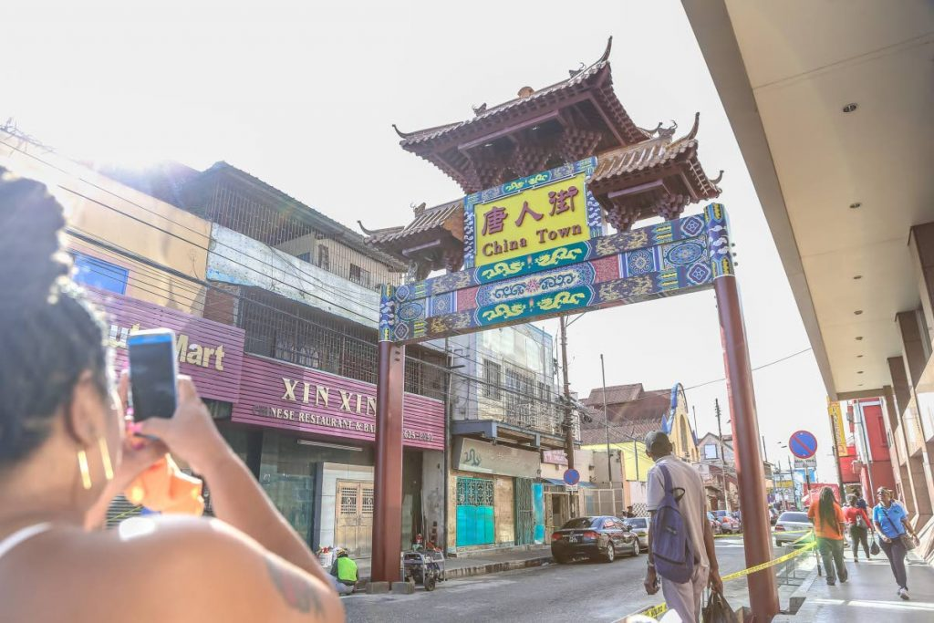 A woman photographs one of the Chinatown arches on Charlotte Street where Chinese businesses located nearby.  Naming the area Chinatown is part of the city's plans to establish commercial ties with the Chinese city of Shanghai. - JEFF K MAYERS