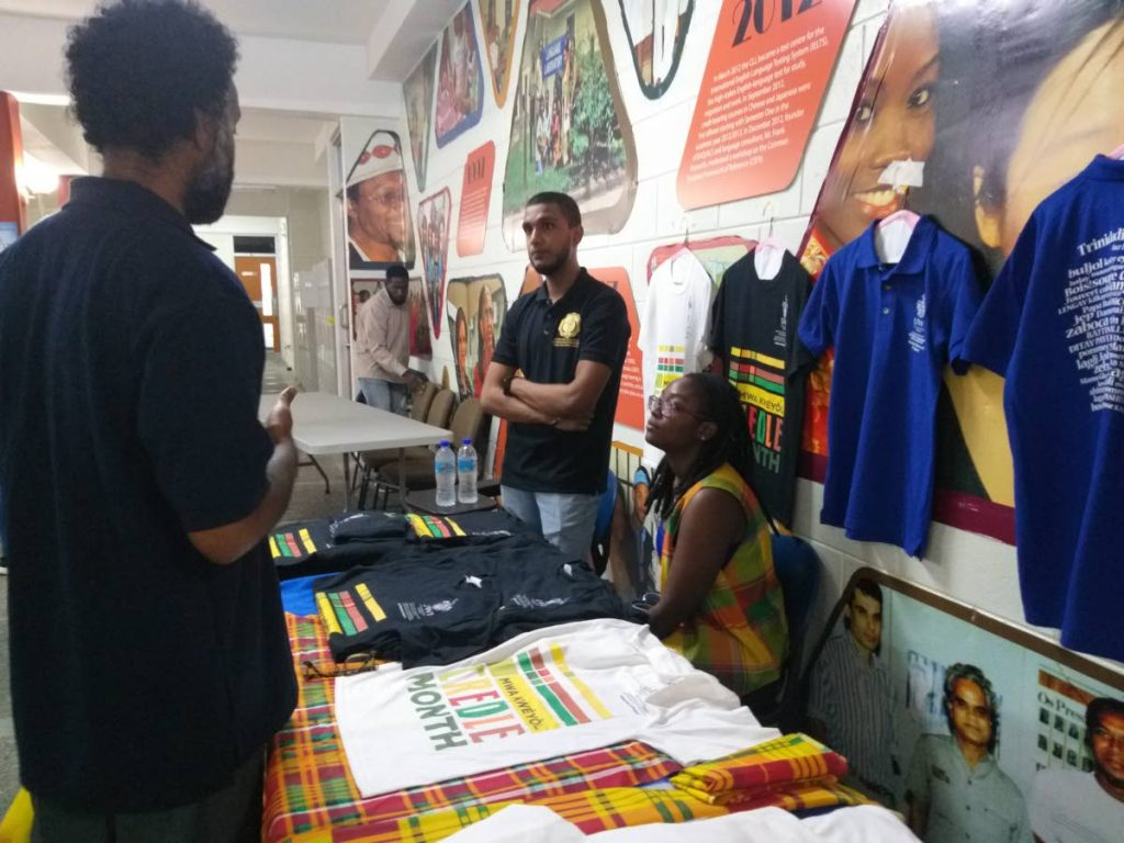 Students of the Department of Modern Languages and Linguistics at the UWI (right) speak to an attendee at UWI's 2019 International Creole Day celebrations. On sale were creole month t-shirts, traditional cocoa tea with bake and saltfish and books on creole history.  - Tyrell Gittens