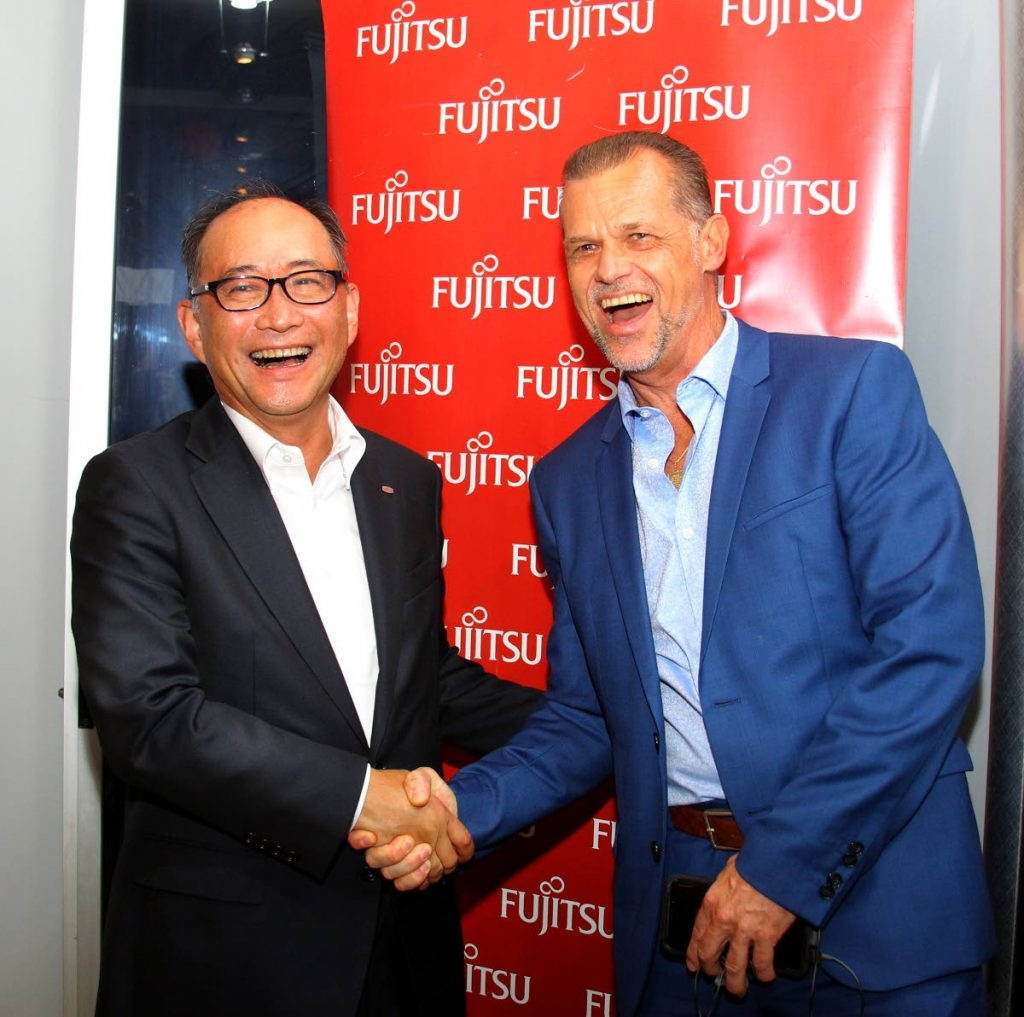 San Kiname Mikito, Fujitsu president and CEO of operations for the Americas, greets Mervyn Eyre, vice president of operations (Caribbean and Latin America). - ROGER JACOB
