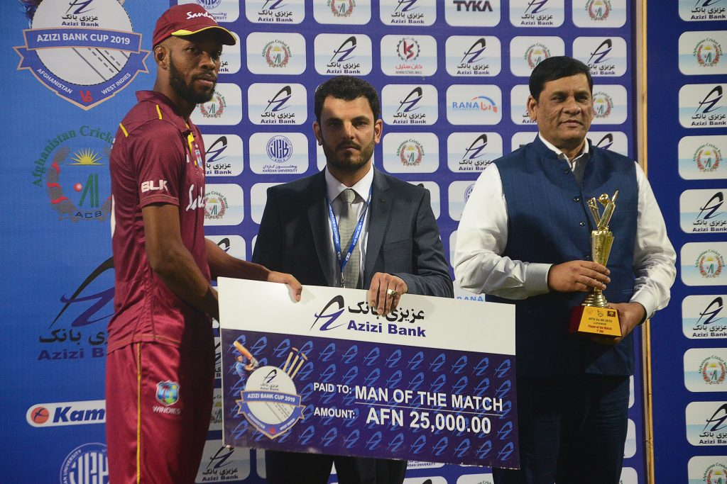 West Indies' Roston Chase (L) receives the 'man of the match' award check after the first one day international (ODI) cricket match between Afghanistan and West Indies at the Ekana Cricket Stadium in Lucknow on November 6, 2019. (Photo by Rohit UMRAO / AFP) / ----IMAGE RESTRICTED TO EDITORIAL USE - STRICTLY NO COMMERCIAL USE-----