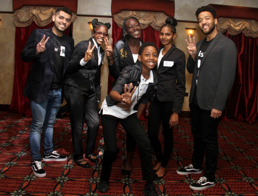 Motivational speakers and facilitators of the WE Youth Conference Joseph Flores, left, and Jalen Nicholson take a photo with students of El Dorado West Secondary School at the The Banquet and Conference Centre Movietowne on Wednesday.  - Ayanna Kinsale